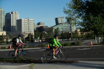 image of bicyclists riding with downtown skyline in backgrou