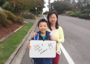 image of mom and son standing on street with placard
