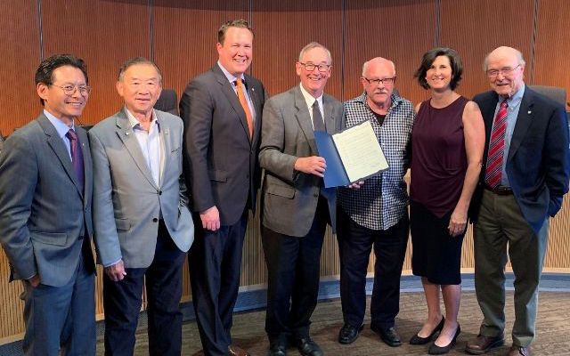 Jim McEachran accepts a commendation from the City Council