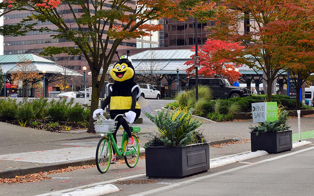 Transportation mascot Pedbee rides a Lime bike on 108th Avenue Northeast.