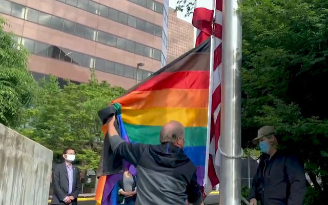 Staff raise a rainbow flag at City Hall for Pride Month.