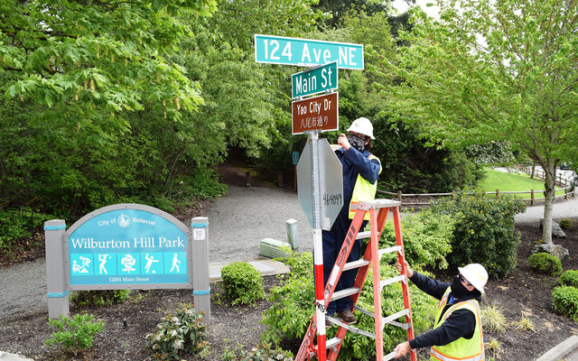 Transportation workers install an honorary street sign celebrating sister city Yao, Japan.