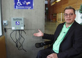 ADA Administrator Blayne Amson shows a wheelchair charging station