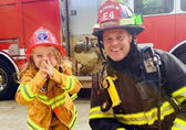 A little girl can't help but smile with a firefighter.