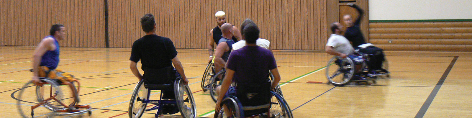 A group of man in wheelchairs playing basketball