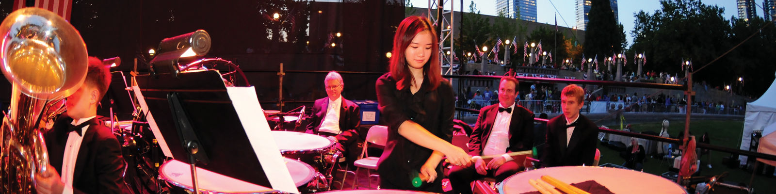 orchestra playing, a woman playing on drums