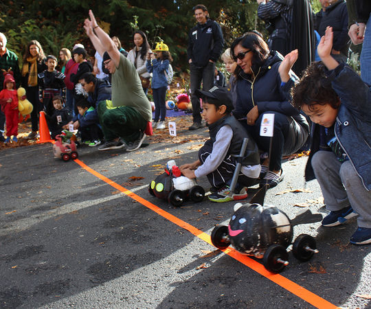 The children are gathered at the starting line with their pumpkin racers.