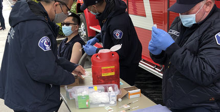 Firefighter-medics administer a COVID-19 vaccine at a pop-up clinic at Downtown Park.
