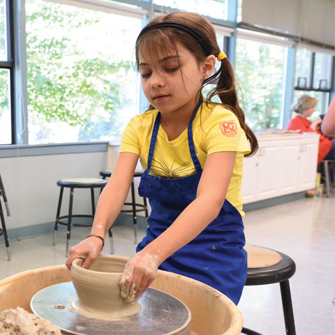 girl in a yellow top and blue skirt doing pottery