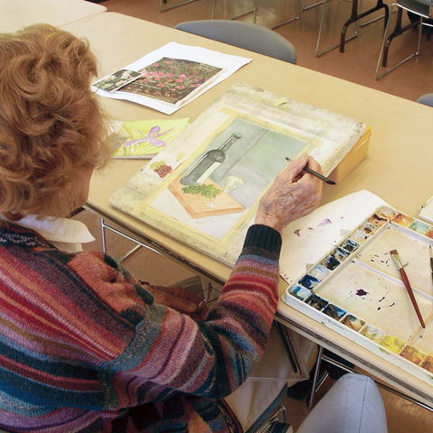 elderly woman painting in a notepad