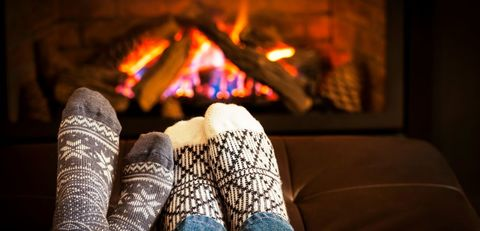 Image of two pairs of feet with socks in front of a fire