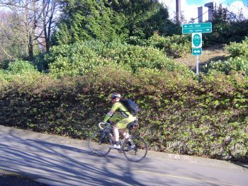 image of bicyclist riding past wayfinding sign