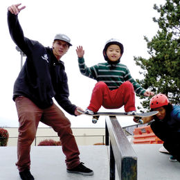Two young adults teaching a child to skateboard