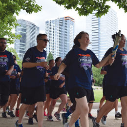 Smiling people running at the Special Olympics torch run