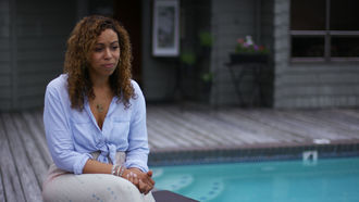 Image of black woman sitting beside a swimming pool.