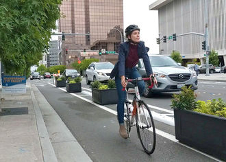 image of person bicycling in downtown on 108th Avenue Northeast