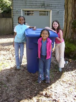 Children standing by recycle cart